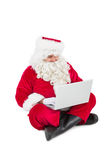 Santa sitting and using his laptop Royalty Free Stock Images