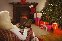 Santa sitting and using laptop on the armchair Stock Images