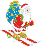 Santa skiing with gifts Stock Images
