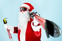 Santa with skis. Photo of happy Santa Claus with skis looking through goggles Stock Image