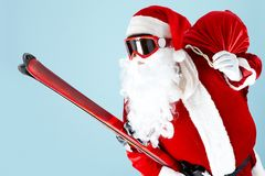 Santa with skis. Photo of happy Santa Claus with skis looking through goggles Stock Images