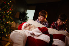 Santa sleeping. Santa Claus sleeping on sofa with two boys looking at him Royalty Free Stock Images