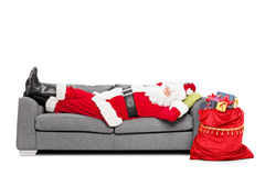 Santa sleeping on sofa. With a bag of presents beside him isolated on white background Stock Photos
