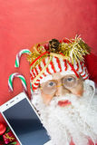 Santa with smartphone and earphones, on red Royalty Free Stock Image
