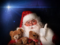 Santa smiling holding toy teddy bears Royalty Free Stock Photo