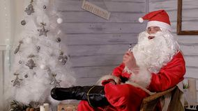 Santa smokes wipe sitting in a chair. 4k Royalty Free Stock Photography