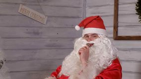 Santa smokes wipe sitting in a chair. 4k Stock Photos