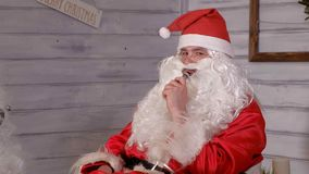 Santa smokes wipe sitting in a chair. 4k Stock Image