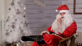 Santa smokes wipe sitting in a chair. 4k Royalty Free Stock Image