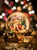 Santa Snow Globe. This is a Santa Snow Globe in front of a Christmas Tree with lights Stock Image