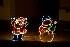 Santa and Snowman. The front lawn of a house decorated with Santa Claus and a snowman during the holiday season royalty free stock images