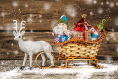 Santa and snowman in a reindeer sleigh with gifts. Stock Photo