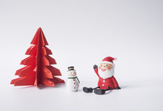 Santa. And snowman sitting in front of red Christmas tree waiting for Christmas Stock Photography