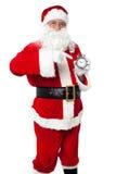 Santa som pekar på ett antikt tidstycke Royaltyfria Bilder