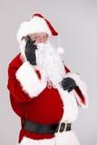 Santa som talar på mobilen som ser kameran Royaltyfri Fotografi