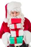Santa sonriente que sostiene la pila de regalos Imagenes de archivo