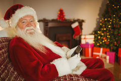 Santa sorridente che per mezzo dello smartphone al natale Fotografie Stock Libere da Diritti