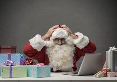 Santa soumise à une contrainte se reliant à son ordinateur portable Images libres de droits