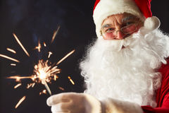 Santa with a sparkler. Portrait of Santa with a sparkler isolated on black Royalty Free Stock Photography