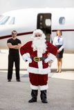 Santa Standing With Bodyguard And Airhostess. Full length portrait of Santa with hands on hip standing against bodyguard; airhostess and private jet stock image