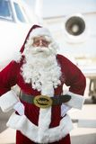 Santa Standing With Hands On Hip Against Private. Portrait of Santa standing with hands on hip against private jet at airport terminal Stock Photo
