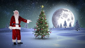 Santa standing in the north pole showing christmas tree stock footage