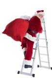 Santa steps up a ladder Royalty Free Stock Images