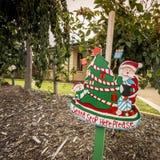 Santa Stop Here Please. Sign in home garden with house peeping through garden plants Stock Photography