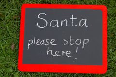 Santa stop here sign on blackoard with red border Royalty Free Stock Images