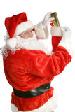 Santa Stuffing Stockings. Santa Claus stuffing a Christmas stocking.  Focus on Santa's face.  Isolated on white Stock Images