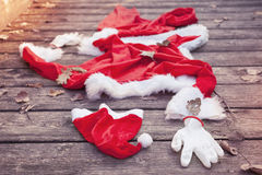 Santa suit abandoned on a wooden floor Royalty Free Stock Images