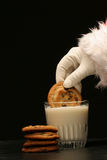 Santa sumerge una galleta en la leche Fotos de archivo libres de regalías