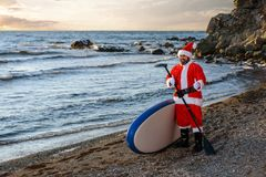 Santa on SUP board. Man in Santa costume with SUP board on winter sea Royalty Free Stock Images