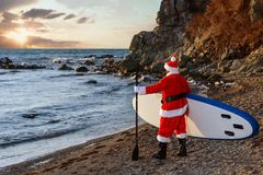 Santa on SUP board. Man in Santa costume with SUP board on winter sea Royalty Free Stock Photo