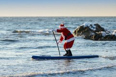 Santa on SUP board. Man in Santa costume with SUP board on winter sea Stock Image