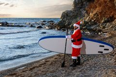 Santa on SUP board. Man in Santa costume with SUP board on winter sea Royalty Free Stock Photos