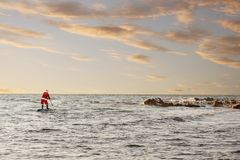 Santa on SUP board. Man in Santa costume with SUP board on winter sea Stock Photography