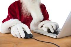 Santa surfs on the internet Stock Image
