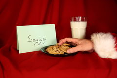 Santa takes a cookie. Milk and cookies on luxurious red tablecloth for Santa who quickly takes one Royalty Free Stock Photos