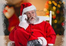 Santa talking on his phone while sitting on a chair Royalty Free Stock Photo