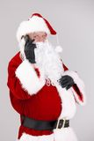 Santa talking on mobile looking at camera Royalty Free Stock Photography