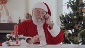 Santa is talking on the phone. Santa Claus with serious face in red costume near bright decorated fir tree and fireplace talking on the cell phone. Old man is stock video