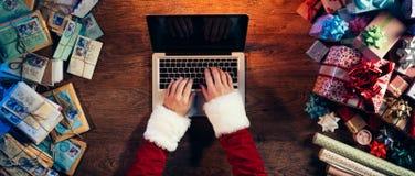 Santa tapant sur un ordinateur portatif Photographie stock libre de droits