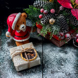 Santa Teddy Bear, Gift box wrapped linen cloth and decorated with  cord, christmas decoration on brown vintage wooden boards backg Royalty Free Stock Image