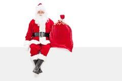 Santa tenant un sac des présents posés sur un panneau Photos stock
