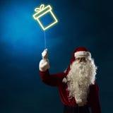 Santa tenant un symbole léger de la boîte de Noël Photos stock