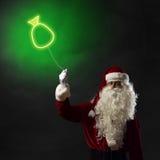 Santa tenant un symbole léger du sac de Noël Photos libres de droits
