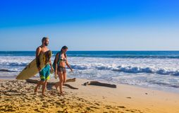 Santa Teresa, Costa Rica - June, 28, 2018: Couple of surfers on the beach of Santa Teresa walking and enjoying the time. Together in a beautiful sunny day with stock photo