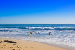 Santa Teresa, Costa Rica - June, 28, 2018: Outdoor view of surfers on the beach of Santa Teresa in a beautiful sunny day. With blue sky and blue water in Costa royalty free stock photo