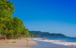 Santa Teresa, Costa Rica - June, 28, 2018: Outdoor view of surfers on the beach of Santa Teresa in a beautiful sunny day. With blue sky and blue water in Costa royalty free stock photos